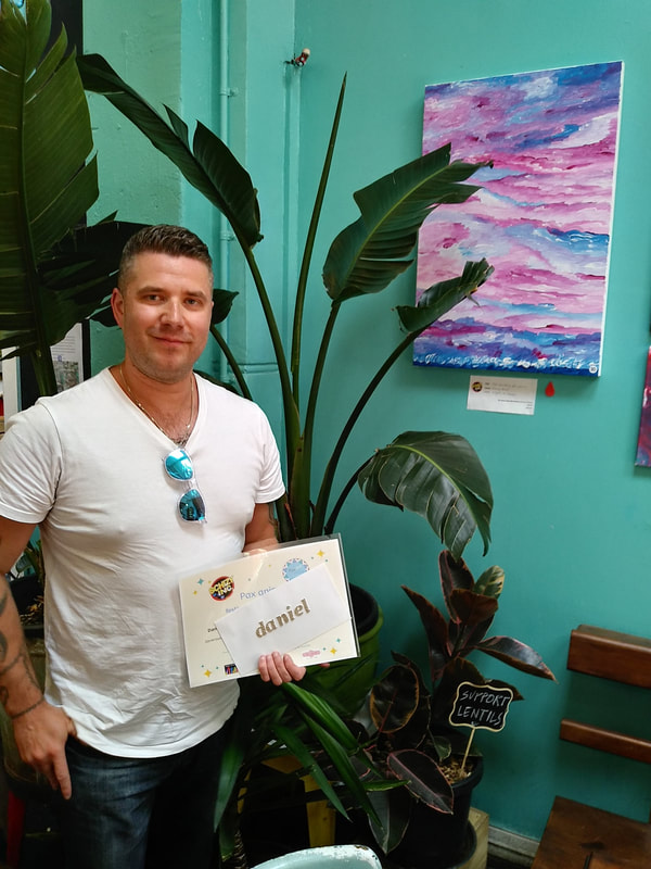 Daniel in front of his work, receiving the Steph's Pick award.